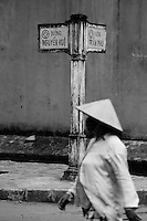 Walking walking along the streets of the old quarter in Hoi An in black & white.