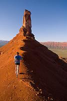 A young woman runs along a ridgeline trail in Castle Valley near Moab, Utah.