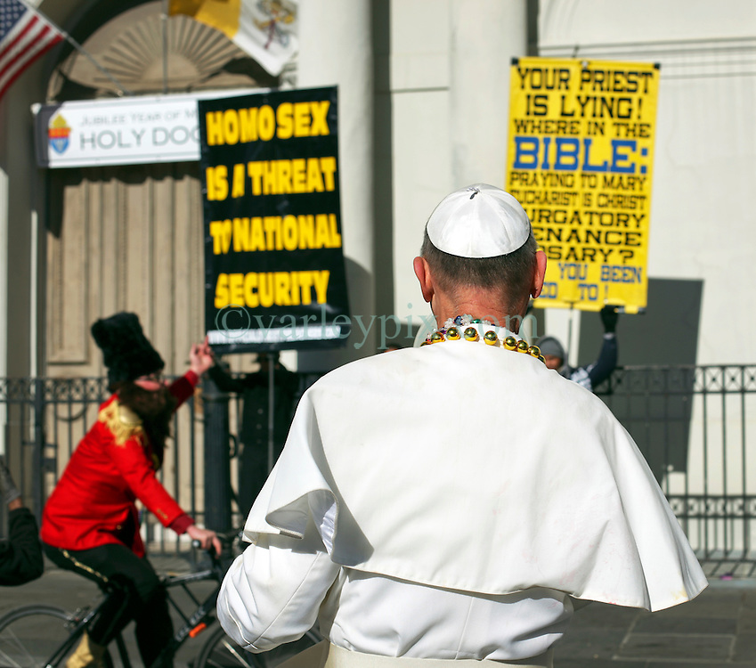 09 February 2016. New Orleans, Louisiana.<br /> Mardi Gras Day.A man dressed as the Pope confronts rude and abusive fundamentalist Christians spewing their messages of hate at St Louis Cathedral. <br /> Photo©; Charlie Varley/varleypix.com