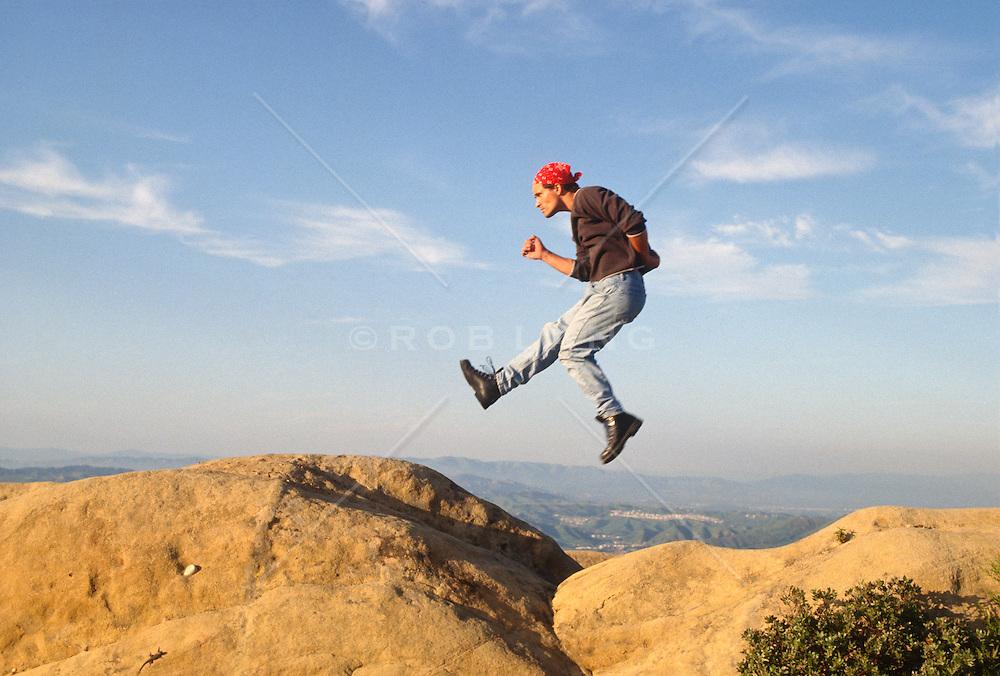 Man leaping from rock to rock in mid air