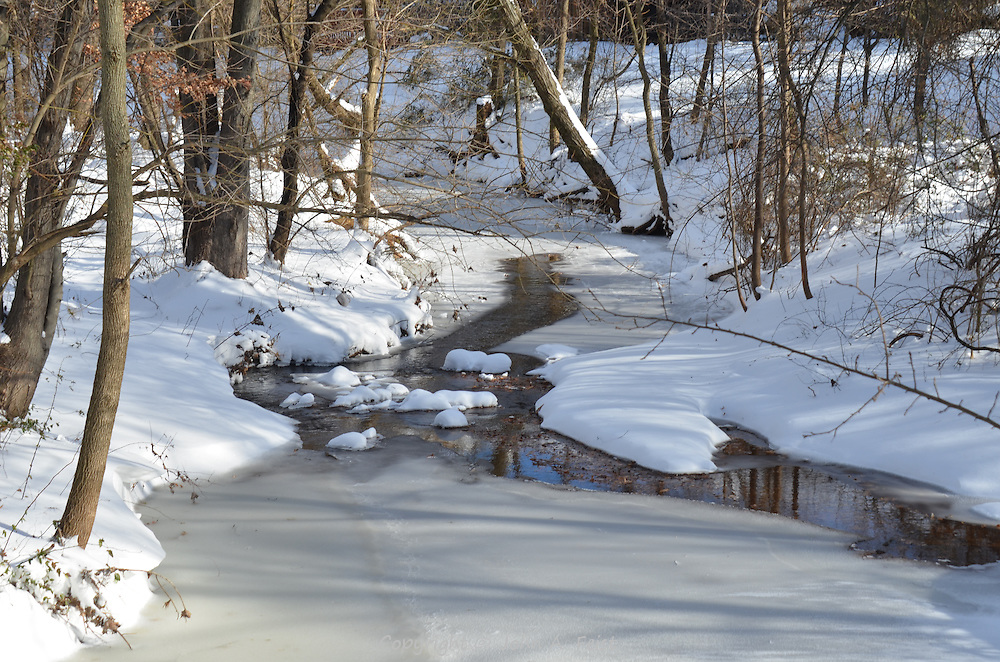 The sun started to warm the stream.  As the ice melted the bright blue sky could be seen in the water.