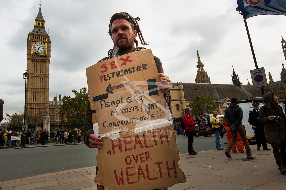"""Parliament Square, London, October 22nd 2014. Protesters from """"Occupy Democracy"""" continue their demonstration against what they say is the hijacking of Britain's democracy by capitalism, where big business is allowed to trample people's rights. Having earlier been removed from Parliament square on grounds that they had damaged the threadbare lawn, they continue to demonstrate outside the closed off space. PICTURED: An activist's placard portrays Westminster """"Sex Pestminster"""" and argues that people matter more than corporations."""