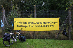 A banner is displayed by Extinction Rebellion climate activists outside an entrance to Farnborough Airport on 2nd October 2021 in Farnborough, United Kingdom. Activists blocked three entrances to the private airport to highlight elevated carbon dioxide levels produced by super-rich passengers using private jets and 'greenwashing' by the airport in announcing a switch to sustainable aviation fuel (SAF).