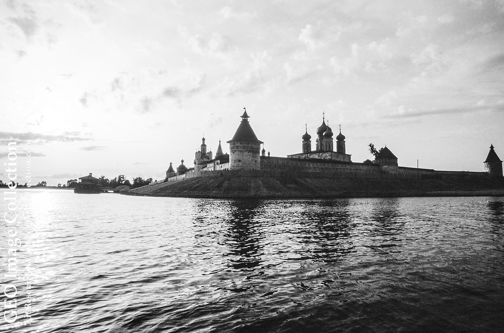 The walls, domes, turrets and towers of the Makarevski Sheltovodskii monastery are silhouetted against a pearly sky at sunset as they rise above the waters of the Volga River. For more information, see the book DOWN THE VOLGA, page 163.