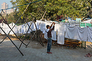 Dhobi wallahs or washermen, hang clothes and linen to dry at the Devi Prasad Sadan Dhobi Ghat in New Delhi, India. The ghat is home to around 64 washermen and is tucked away on a quiet street called Hailey Lane in the very centre of the city behind Connaught Place. The ghat relies on a borewell for water, chilamchis cement tubs, hauds tanks, naandis pools and huge electric spinners that wring out water.