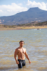 shirtless muscular man in a lake