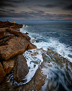 A lone couple in the distance watching the rising tide at Portland Bill in Dorset