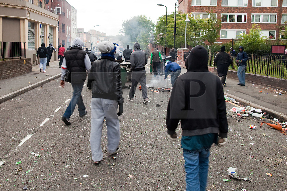 © Licensed to London News Pictures . FILE PICTURE DATED 08/08/2011. Hackney , UK . Rioters throw bricks and rocks at a line of riot police on Clarence Road . People riot and loot on the Pembury Estate in Hackney . Following a night of riots and looting in Tottenham , rioting and looting spreads to other areas . Photo credit : Joel Goodman/LNP