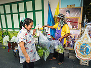 10 AUGUST 2016 - BANGKOK, THAILAND: A man who sells vegetables from a push cart in Bangkok sets up in front of a portrait of Queen Sirikit of Thailand. Thais are preparing for the Queen's birthday. Queen Sirikit of Thailand, was born Mom Rajawongse Sirikit Kitiyakara on 12 August 1932. She married  Bhumibol Adulyadej, King of Thailand (Rama IX) in 1950. He is the longest serving monarch in the world and she is longest serving consort of a monarch. Her birthday, like the King's Birthday (which falls on Dec. 5),  is a national holiday in Thailand. Her birthday, August 12, is also celebrated as Mothers' Day in Thailand. Thais hang portraits of Queen Sirikit in their homes and fly her royal flag on her birthday.        PHOTO BY JACK KURTZ