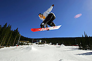 Scott Hoffman, 29, of Lakewood, Co. gets airborne off the big kicker at Echo Mountain Park near Evergreen on Sunday April 9, 2006 seemingly hanging in the air above the skyline and lodge at the ski and snowboard area. Echo Mountain Park is Colorado's first terrain-park only ski and snowboard area and features numerous rails, obstacles and jumps on the site of the former Squaw Pass Ski Area in the Arapaho National Forest near Mount Evans. The area opened recently and is hoping to attract a younger crowd with cheaper tickets, music, contests and a shorter and easier drive from Denver. Hoffman is also an employee at Echo Mountain Park and was riding in his free time..(MARC PISCOTTY/ © 2006)