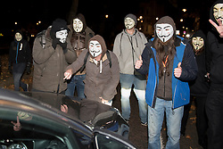 © Licensed to London News Pictures. 05/11/2016. London, UK. Participants wearing Guy Fawkes style masks take part in the Million Mask March in central London, blocking the path of a bemused motorist, amidst a heavy police presence. Photo credit : Stephen Chung/LNP