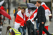 Some of the protestors rush to take shelter due to torrential rain during a protest against Viktor Lukashenko regime of Belarus outside Westminster Palace, Houses of Parliament in London on Sunday, Aug 8, 2021. Protestors joined by Polish people gathered to mark the 1st anniversary of the 2020 presidential elections, which opponents claim were rigged. Protestors also called Government in Britain to do more against the repressive regime of Lukashenko. (VX Photo/ Vudi Xhymshiti)
