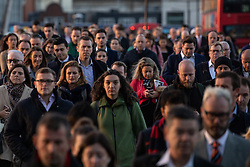 © Licensed to London News Pictures. 24/10/2018. London, UK. Commuters cross London Bridge at sunrise. The UK is set to experience a cold weather front later this week. Photo credit : Tom Nicholson/LNP