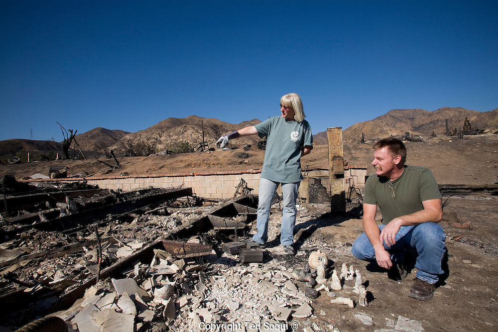 Tim and Cindy Snow look through the ashes of their former home for any belongings that survived the fire..Residents of the Oakridge Mobile Home Park in Sylmar, CA return to their homes, most of the over 500 homes were lost to fire. Several residents sifted through the ashes to find their personal belonging and sacred momentos. Many residents said they would not return to living at the park.