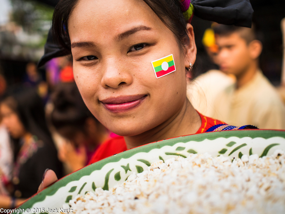 """05 APRIL 2015 - CHIANG MAI, CHIANG MAI, THAILAND: A Tai Yai woman with a Burmese flag decal on her cheek carries flower buds to throw to boys being ordained as Buddhist novices during the second day of the three day long Poi Song Long Festival in Chiang Mai. The Poi Sang Long Festival (also called Poy Sang Long) is an ordination ceremony for Tai (also and commonly called Shan, though they prefer Tai) boys in the Shan State of Myanmar (Burma) and in Shan communities in western Thailand. Most Tai boys go into the monastery as novice monks at some point between the ages of seven and fourteen. This year seven boys were ordained at the Poi Sang Long ceremony at Wat Pa Pao in Chiang Mai. Poy Song Long is Tai (Shan) for """"Festival of the Jewel (or Crystal) Sons.    PHOTO BY JACK KURTZ"""