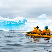 Kayakers in a tandem kayak paddle into an iceberg graveyard in a cove at Melchior Island on the western side of the Antarctic Peninsula.