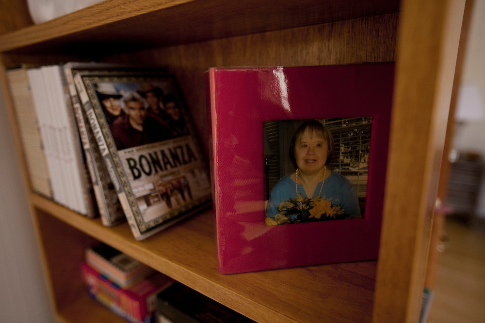 """A photo of Mary Beth Solinski, a 59 year old, with Down Syndrome, sits on the bookshelf next to her favorite DVDs of the television show """"Bonanza""""...Aging adults with Down Syndrome. In 1983, people with Down syndrome could expect to live to age 25. Today, their life expectancy is 60 years. We interview a 59-year-old patient who has outlived her parents and is now in AARP. She has trouble walking, but has lots of interests, such as cooking, arts and crafts and reading."""