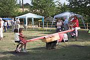 Children play on See-saw, Hasketon Village summer fete, Suffolk, England