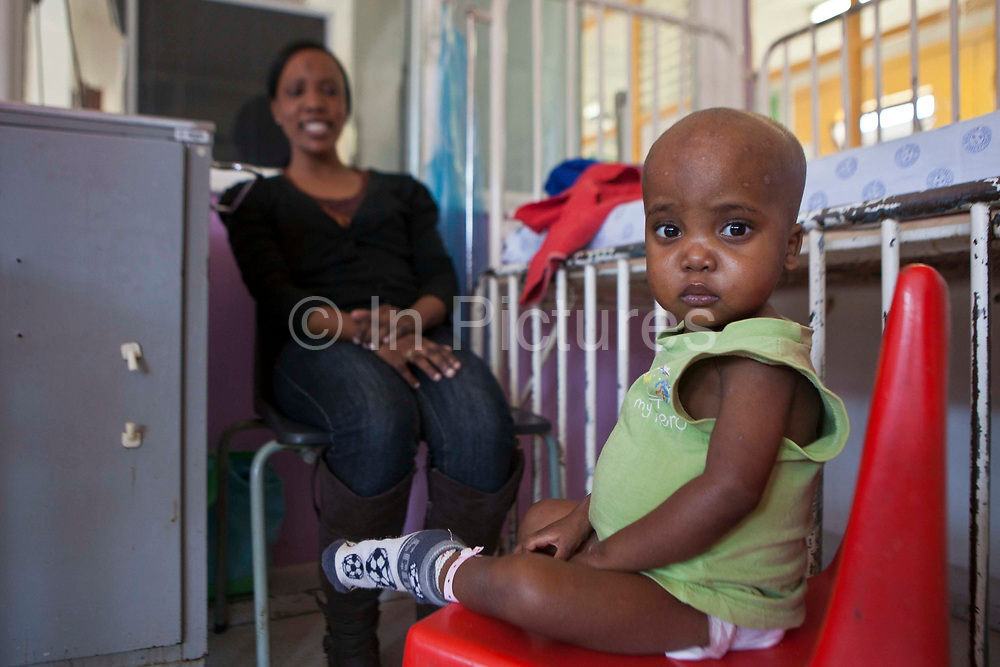This young child sits on a chair next to their cot bed with their mother in Baragwanath Hospital in Johannesburg, South Africa.   The child is dying and receiving palliative care from the Bigshoes Foundation.  Baragwanath is the third biggest hospital in the world, and the first hospital that BigShoes has provided palliative care to, a service that was previously non existent in South Africa. They now offer these services in Kwazulu Natal, Western Cape and Guateng.