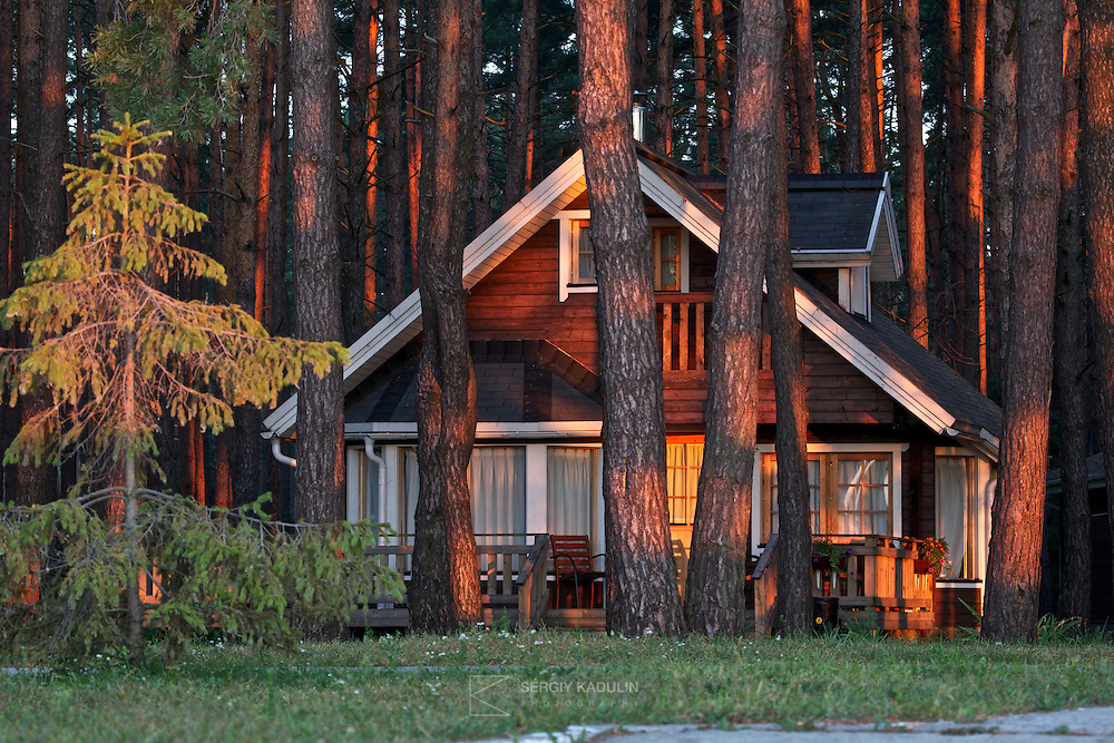 Residential and recreation real estate Glebovka, Ukraine. Two-bedroom house in the forest is shot during sunrise, to make light warm and mild.