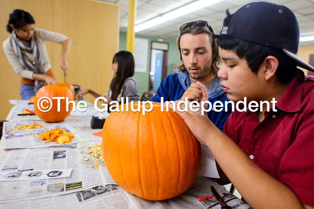 102514       Cable Hoover<br /> <br /> Isaiah Lynch, right, and Lane Towery carve a pumpkin together during a Big Brothers Big Sisters event at the Hozho Center in Gallup Saturday.