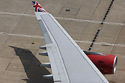 Aerial view (from control tower) of Virgin Atlantic airliner's wing and engine at London Heathrow airport. <br /> Taxiing along the centreline that helps pilots navigate to specific locations around the airport consisting of five terminals on a site that covers 12.14 square kilometres (4.69 sq mi). London Heathrow is a major international airport, the busiest airport in the United Kingdom and the busiest airport in Europe by passenger traffic. It is also the third busiest airport in the world by total passenger traffic, handling more international passengers than any other airport around the globe.