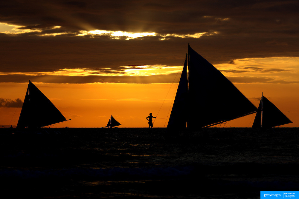 Asian tourists enjoy boat rides during an amazing sunset at White Beach,  Boracay Island, the Philippines on September 29, 2008, Photo Tim Clayton.....Asian tourists at White Beach, Boracay Island, the Philippines...The 4 km stretch of White beach on Boracay Island, the Philippines has been honoured as the best leisure destination in Asia beating popular destinations such as Bali in Indonesia and Sanya in China in a recent survey conducted by an International Travel Magazine with 2.2 million viewers taking part in the online poll...Last year, close to 600,000 visitors visited Boracay with South Korea providing 128,909 visitors followed by Japan, 35,294, USA, 13,362 and China 12,720...A popular destination for South Korean divers and honeymooners, Boracay is now attracting crowds of tourists from mainland China who are arriving in ever increasing numbers. In Asia, China has already overtaken Japan to become the largest source of outland travelers...Boracay's main attraction is 4 km of pristine powder fine white sand and the crystal clear azure water making it a popular destination for Scuba diving with nearly 20 dive centers along White beach. The stretch of shady palm trees separate the beach from the line of hotels, restaurants, bars and cafes. It's pulsating nightlife with the friendly locals make it increasingly popular with the asian tourists...The Boracay sailing boats provide endless tourist entertainment, particularly during the amazing sunsets when the silhouetted sails provide picture postcard scenes along the shoreline...Boracay Island is situated an hours flight from Manila and it's close proximity to South Korea, China, Taiwan and Japan means it is a growing destination for Asian tourists... By 2010, the island of Boracay expects to have 1,000,000 visitors.
