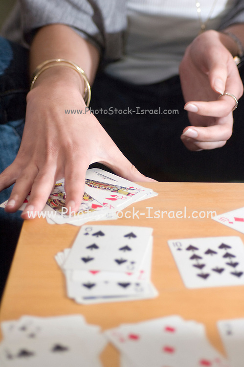 Mature woman of 70 playing solitaire with a pack of cards - Model Release available