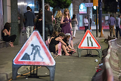 © Licensed to London News Pictures . 15/06/2014 . Manchester , UK . Women sit on the pavement by roadworks . People on a night out in Manchester City Centre overnight , following England's defeat to Italy in the World Cup . Photo credit : Joel Goodman/LNP