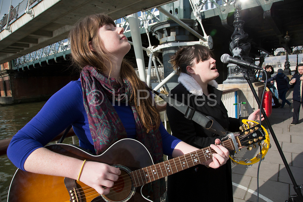 Buskers performing near Hungerford Bridge. Duo playing guitar and singing harmonies to old Joni Mitchell songs. The South Bank is a significant arts and entertainment district, and home to an endless list of activities for Londoners, visitors and tourists alike.