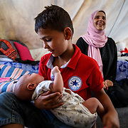 Yahya, 11, a refugee from Idlib, Syria, holds his baby brother, Ahmed, 25 days, who was born in the camp. Their mother, Hanan, 33, is in the background. Ritsona Refugee Camp, Greece. July 2016.