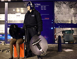 © Licensed to London News Pictures.  FILE PICTURE DATED 08/08/2011 LONDON, UK. A policeman guards a suspected looter, wearing a Currys' staff fleece, after she was caught inside the Brixton Branch of the UK electrical chain. The looting took place after a second night of violence hit several parts London. Photo credit: Matt Cetti-Roberts/LNP