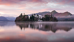 © Licensed to London News Pictures. 01/12/2020. Keswick UK. The sky glows purple & pink at dawn this morning in Keswick, Cumbria, as Derwent Isle & the surrounding mountains reflect into the calm water of Derwent Water. Photo credit: Andrew McCaren/LNP