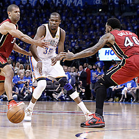 12 June 2012: Oklahoma City Thunder small forward Kevin Durant (35) passes the ball past Miami Heat small forward Shane Battier (31) and Miami Heat power forward Udonis Haslem (40) during the second half of Game 1 of the 2012 NBA Finals between the Heat and the Thunder, at the Chesapeake Energy Arena, Oklahoma City, Oklahoma, USA.