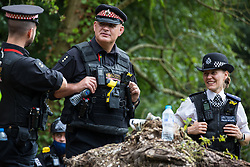 Denham, UK. 24 July, 2020. Police officers from City of London Police and the Metropolitan Police chat alongside the river Colne during a large policing operation also involving Thames Valley Police and Hampshire Police to prevent environmental activists from HS2 Rebellion from attempting to hinder the destruction of an ancient alder tree in connection with works for the HS2 high-speed rail link in Denham Country Park.