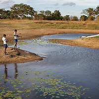Brothers M. Siranjeevithan, 13 (left), and M. Chandrakumar, 11, fish at reservoir close to their home. Their catch will supplement their mother's income.<br /> <br /> Brothers M. Siranjeevithan, 13, and M. Chandrakumar, 11, attend Vadamunai Government Tamil Mixed School. Their father was killed, an innocent bystander in the conflict between the LTTE and Sri Lankan Government 11 years ago. The brothers' mother cares for them though they must both fish to supplement the family income. M. Siranjeevithan and M. Chandrakumar live with their mother in one of a dozen temporary makeshift shelters housing conflict-displaced Tamil families located 3km from the Vadamunai Government Tamil Mixed School.<br /> <br /> After fighting between the LTTE and Colombo Government forced displacement of the local Tamil community, the Vadamunai Government Tamil Mixed School was closed in 2007. Since reopening in January 2009, the school has six teaching staff for 88 pupils. Before closure, 136 pupils studied at the school. Five classes are held in a Unicef supplied Temporary Learning Space. Four other classes are conducted outside. Many of the students suffer with the trauma and stress associated with those living in conflict situations. The staff must deal with these issues as well as the personal difficulties that they also themselves suffer living in a conflict environment. <br /> <br /> Photo: Tom Pietrasik<br /> Batticaloa District, Sri Lanka<br /> September 30th 2009