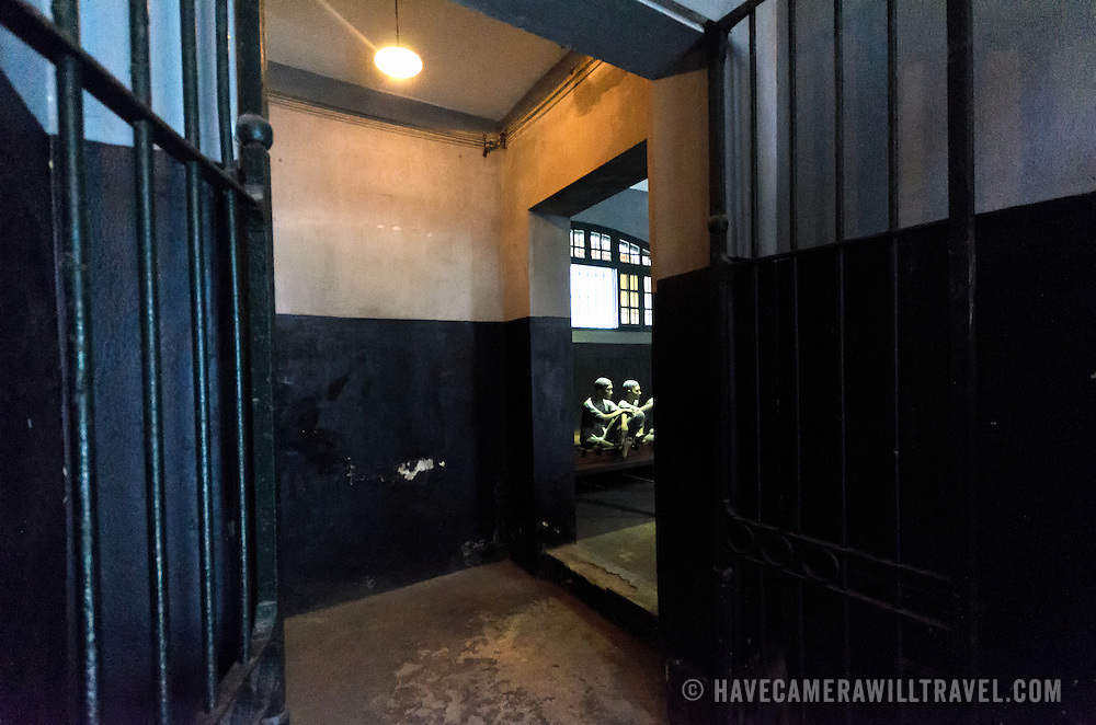 A view through a corridor in Hoa Lo Prison. Through the iron gates can be seen plastic dummies illustrating the conditions that prisoners were kept in by the French colonial government. The prison is better known in the West as the Hanoi Hilton, the place that American pilots were kept as POWs during the Vietnam War.