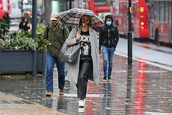 © Licensed to London News Pictures. 03/11/2020. London, UK. A woman wearing a face covering shelters from heavy rainfall underneath an umbrella in north London. The Met Office forecasts rain and strong winds in the South East of England. Photo credit: Dinendra Haria/LNP