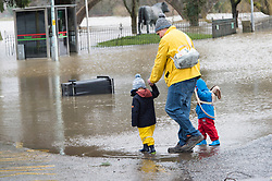 © Licensed to London News Pictures. 10/03/2020. Builth Wells, Powys, Wales, UK. A man with toddlers walks near flood water on the A483 road after the river Wye levels rose dramatically overnight following heavy rainfall in Mid Wales yesterday and last night. According to Natural Resources Wales website, the level reached a peak of 4.21 metres. The website also shows that an all time high level of 5.05 metres was reached at the Builth Wells gauge on 16th February 2020. Photo credit: Graham M. Lawrence/LNP