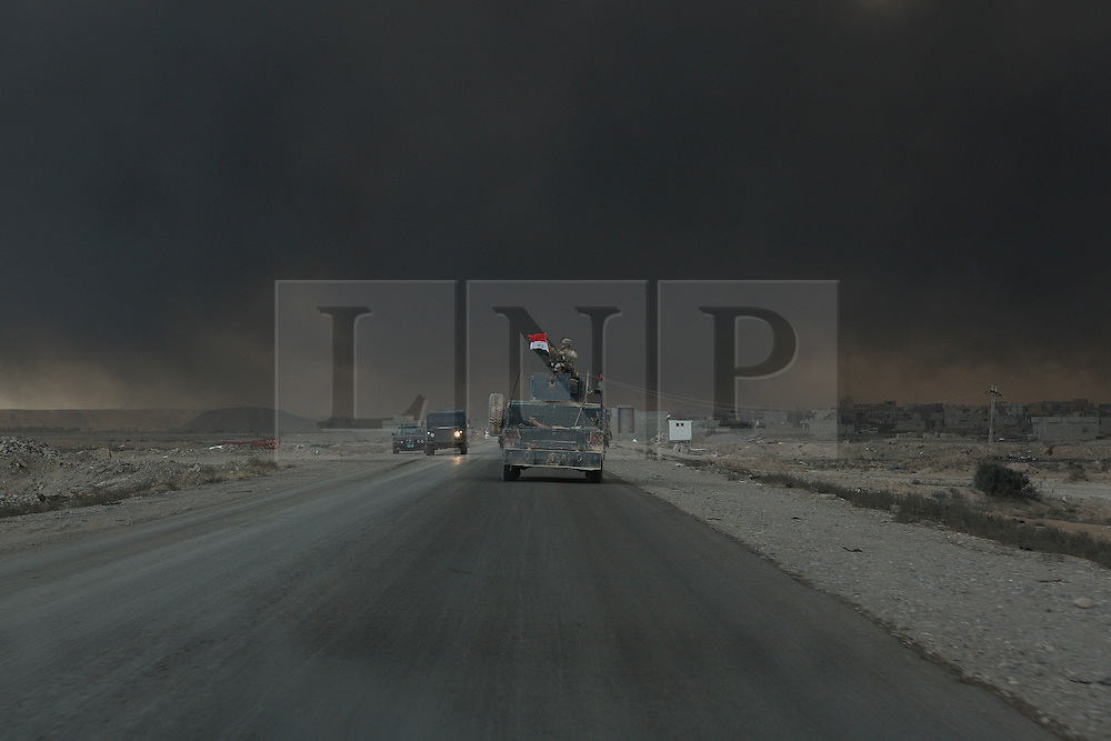 Licensed to London News Pictures. 02/11/2016. Qayyarah, Iraq. With the sky blotted out by burning oil wells, a soldier of the Iraqi Army's Emergency Response Unit holds up the Iraqi flag from the top of an armed Humvee utility vehicle as his convoy enters the town of Qayyarah, Iraq.<br /> <br /> Two months after being liberated from the Islamic State, the Iraqi town of Qayyarah, located around 30km south of Mosul, is still dealing with the environmental repercussions of their ISIS occupation. The town's estimated 15,000 inhabitants constantly live under, and in, heavy clouds of smoke which often envelope the settlement. The clouds emanate from burning oil wells in a nearby oil field that were set alight by retreating ISIS extremists after a two year occupation. The proximity of the fires, often right next to homes within the town, covers many buildings and residents with thick soot and will lead to long term health and environmental implications. Photo credit: Matt Cetti-Roberts/LNP
