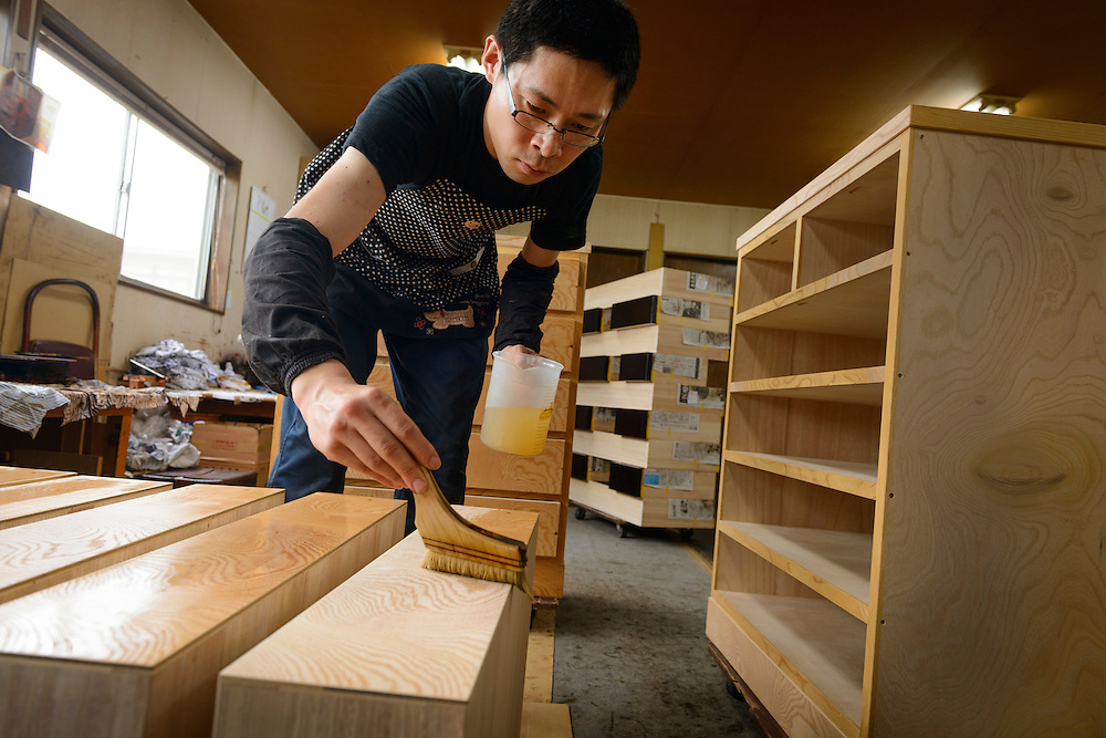 An artisan applying clear lacquer to a chest of drawers, Iwayado Tansu Seisakujo, Oshu City, Iwate Prefecture, Japan, July 18, 2013. Iwayado Tansu chests of drawers have been made in the city of Oshu since the 1780s. They are noted for their fine lacquer finish and finely-wrought metalwork fittings.