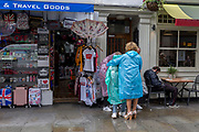 Next to a sleeping man, a tourist family put on plastic rain macs in front of a souvenir shop in Central London, on 15th June 2019, in London, England.