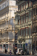 Reflected light from a nearby plate glass building, illuminates older era architecture on Dukelskych hrdinu street, Holesovice district, Prague 7, on 19th March, 2018, in Prague, the Czech Republic.