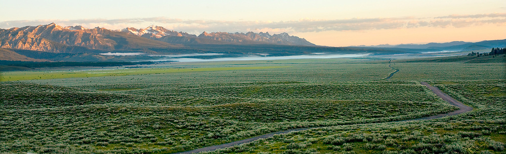 Limited Editions of 8 <br /> Sawtooth Valley panorama from an old ranch road on an early spring morning with hanging valley clouds and Sawtooth Mountain Range in the distance.