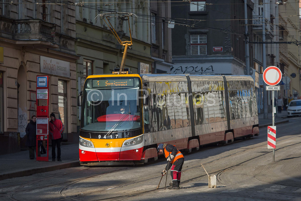 A workman clears debris and dirt from between rails on Milady Horakove street, Holesovice district, Prague 7, on 19th March, 2018, in Prague, the Czech Republic.