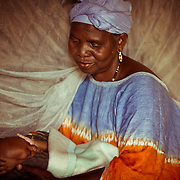 A Koumbadiouma grandmother prepares to put her grandchild to sleep under a mosquito net. In recent times, mosquito net uptake has been one of USAID's most significant success stories in Senegal. The Peace Corps played a big role in the project's implementation.