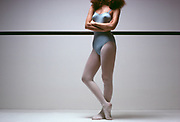 Woman ballet dancer standing at the exercise dance bar with arms crossed