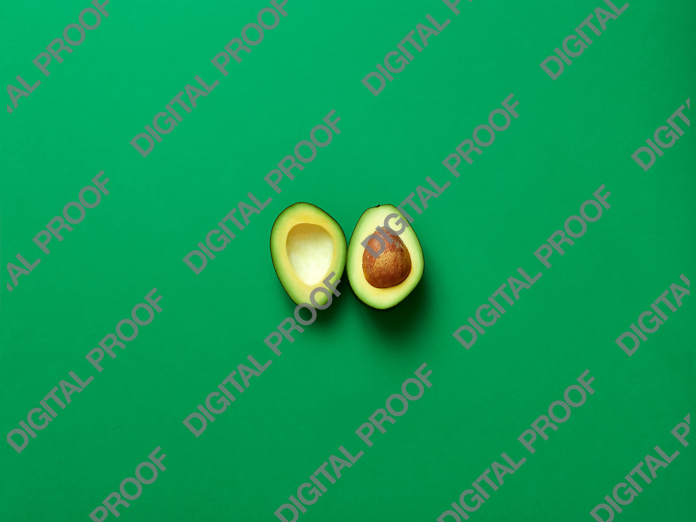 Avocado sliced with seed isolated in green background viewed from above - flatlay look