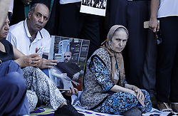 A man holds portrait of a jailed journalist as a woman sits on July 24, 2017 during a demonstration in front of Istanbul's courthouse. Seventeen directors and journalists from Turkey's opposition Cumhuriyet newspaper went on trial on July 24 charged with terror-related offences in what is seen as a key test of press freedoms under President Recep Tayyip Erdogan. Photo by Can Erok/DHA/Depo Photos/ABACAPRESS.COM