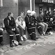 NLD/Huizen/19910721 - Uitgebrande pand kookwinkel DIMA Oude Raadhuisplein Huizen, brandweer mannen rusten uit